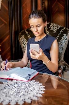 Sérieuse jeune femme d'affaires caucasienne utilise smartphone assis dans le fauteuil et travaillant au bureau à domicile