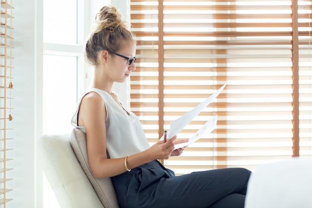 Sérieuse jeune femme d'affaires travaillant avec des papiers