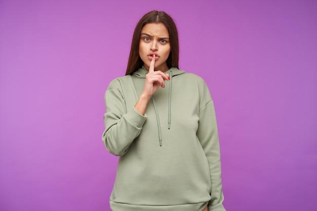 Sérieuse jeune femme aux cheveux longs attrayante avec un maquillage naturel fronçant les sourcils tout en gardant l'index sur sa bouche, isolé sur mur violet