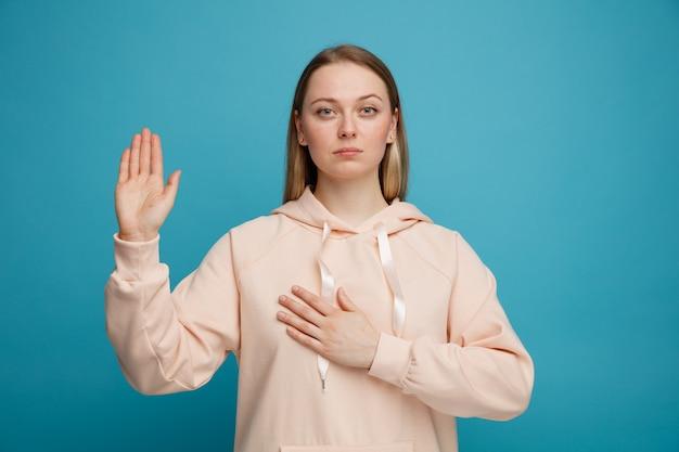 Sérieuse jeune femme blonde faisant le geste de promesse