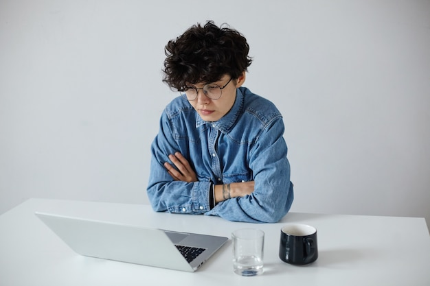 Sérieuse jeune femme bouclée aux cheveux assez sombre avec une coupe courte à la mode en pliant ses mains sur le comptoir et en regardant l'écran de son ordinateur portable avec un visage concentré, isolé