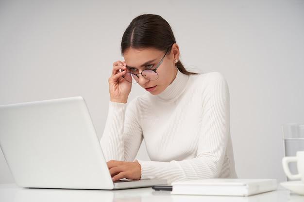 Sérieuse jeune femme brune attrayante avec un maquillage naturel travaillant avec son ordinateur portable au bureau, portant poloneck tricoté blanc et lunettes tout en posant sur un mur blanc