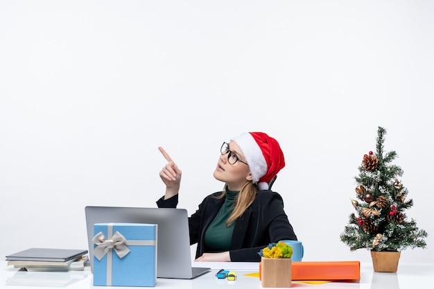 Sérieuse jeune femme avec chapeau de père noël et lunettes assis à une table avec un arbre de noël et un cadeau sur elle sur fond blanc