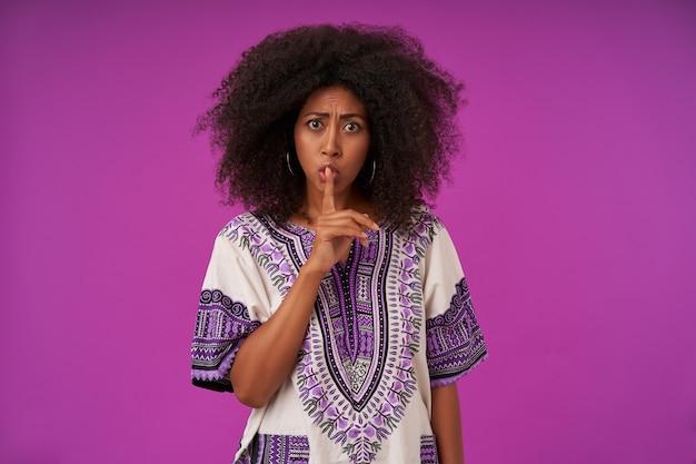 Sérieuse jeune femme à la peau sombre avec une coiffure décontractée posant sur violet, fronçant les sourcils et levant l'index en geste silencieux, vêtue d'une chemise à motifs blancs