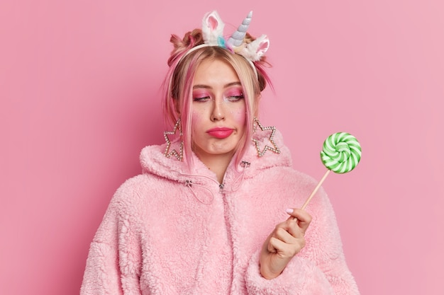 Sérieuse jeune femme triste au régime a la tentation de manger des bonbons