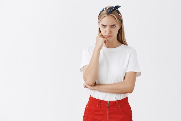 Sérieuse jeune fille blonde concernée posant contre le mur blanc
