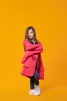 Sérieuse jeune fille en veste surdimensionnée avec les mains croisées