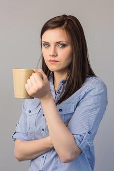 Sérieuse jolie brune tenant une tasse de café