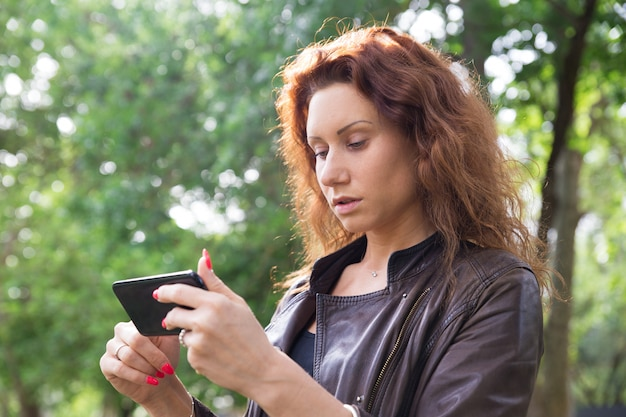 Sérieuse jolie dame naviguant sur smartphone dans le parc de la ville