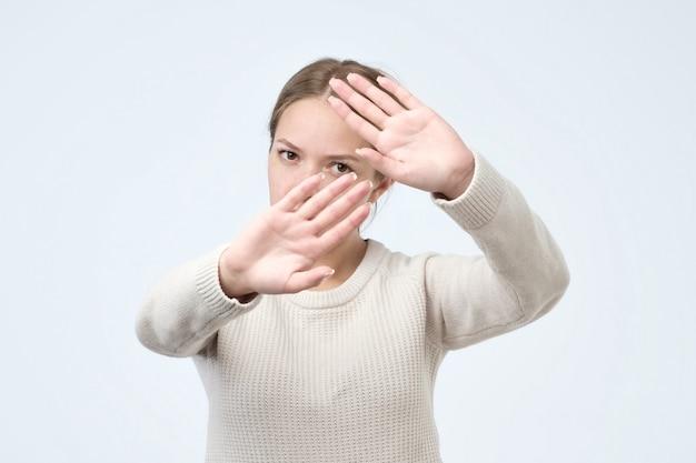 Sérieuse jolie femme faisant le geste de la main d'arrêt