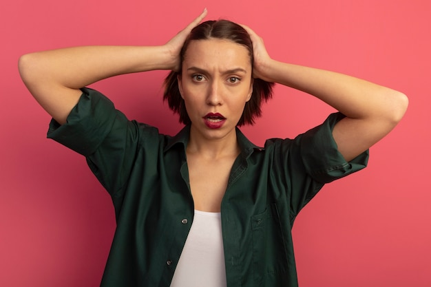 Sérieuse jolie femme tient la tête isolée sur un mur rose