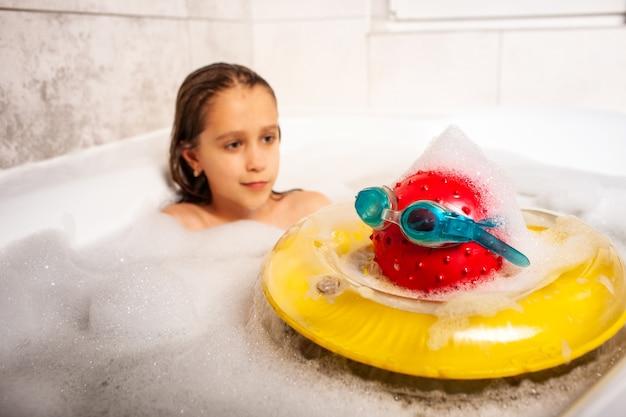 Sérieuse petite fille mignonne se baigne dans un bain moussant et joue avec des jouets