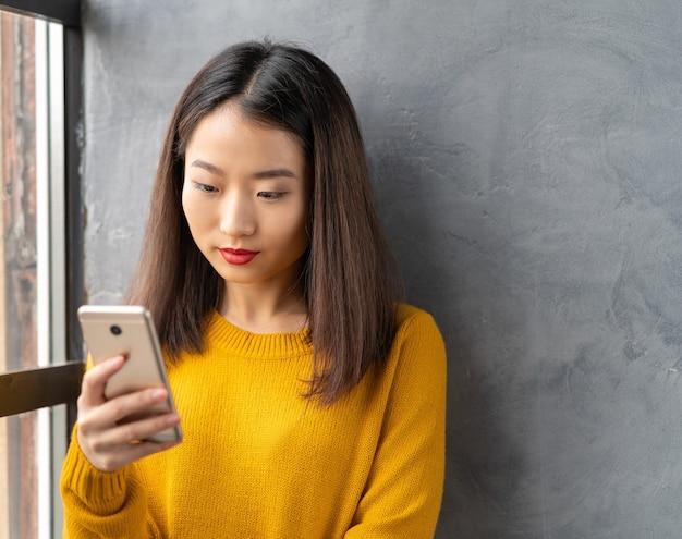 Sérieuse, réfléchie belle jeune femme asiatique regardant le téléphone mobile.