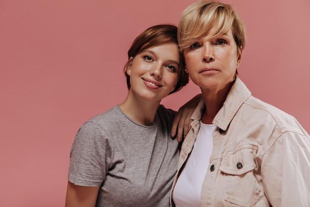 Sérieuse vieille femme aux cheveux blonds en veste cool regardant dans la caméra avec une fille souriante aux cheveux brune en t-shirt gris sur fond rose.