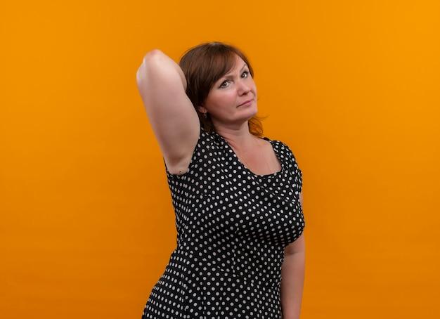 Sérieusement à la femme d'âge moyen mettant la main derrière sur un mur orange isolé avec copie espace