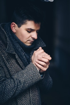 Sérieusement jeune homme en manteau chaud dans une rue sombre