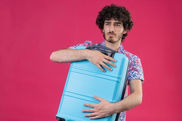 Sérieusement à la recherche de jeune beau voyageur bouclé homme tenant valise sur un espace rose isolé avec copie espace
