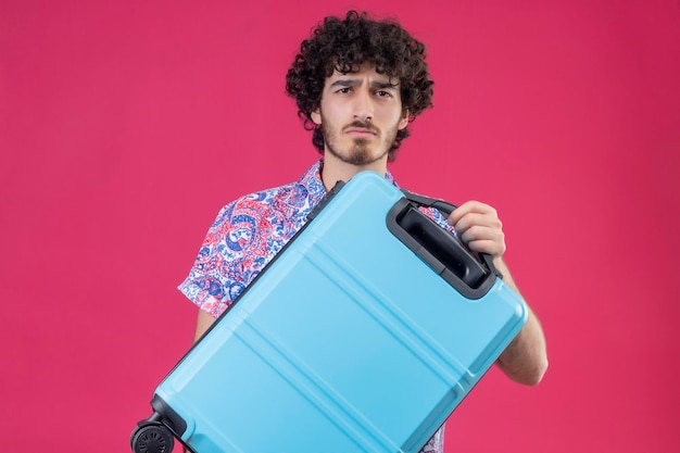 Sérieusement à la recherche de jeune beau voyageur bouclé homme tenant valise à la recherche sur l'espace rose isolé