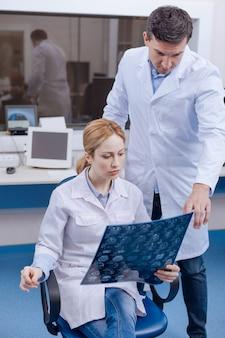 Sérieux agréable femme agréable tenant une image aux rayons x et consulter son collègue tout en recherchant des tumeurs cérébrales