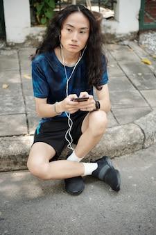 Sérieux beau jeune homme asiatique aux cheveux bouclés assis sur le trottoir et écoutant un message audio dans des écouteurs à l'extérieur