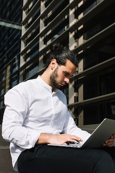 Sérieux bel homme d'affaires assis à l'extérieur du bureau en tapant sur un ordinateur portable