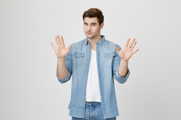 Sérieux bel homme montrant le geste d'arrêt, lever les mains en désaccord