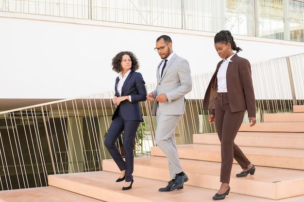 De sérieux collègues marchant ensemble dans leur bureau