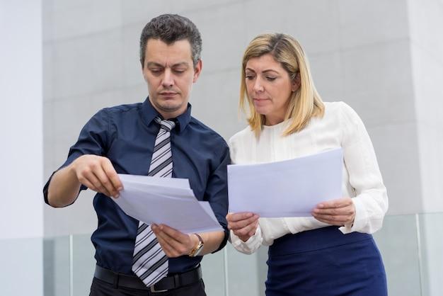 Sérieux collègues masculins et féminins discutant des documents à l'extérieur.
