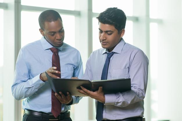 De sérieux collègues multiethniques discutant d'un document