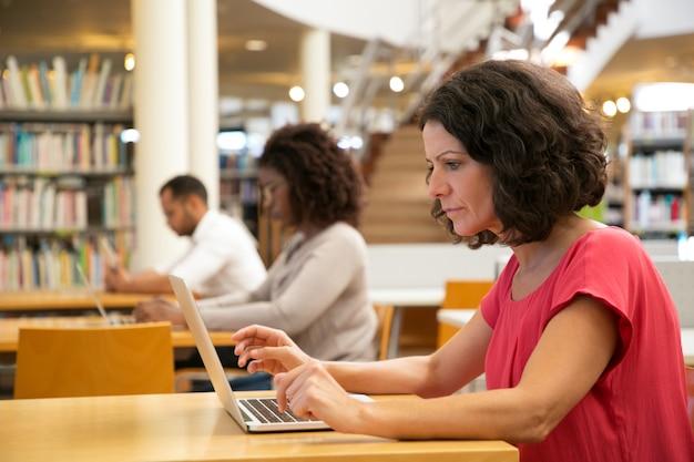 Sérieux concentré femme d'âge moyen travaillant sur la recherche