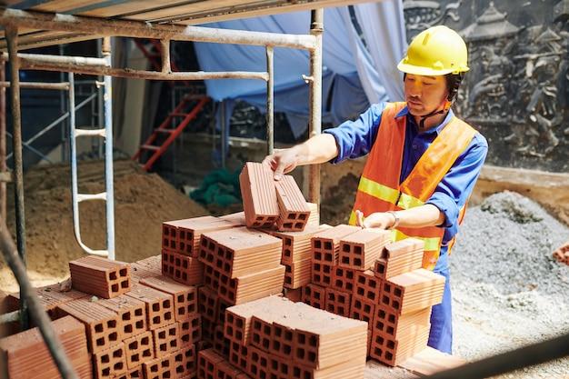 Sérieux constructeur vietnamien en casque prenant des briques orange de pile sur chantier