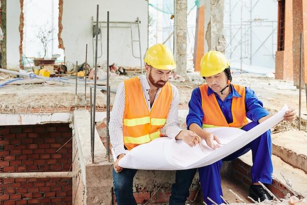 Sérieux constructeurs multiethniques assis dans la salle de l'immeuble en construction et discuter du plan