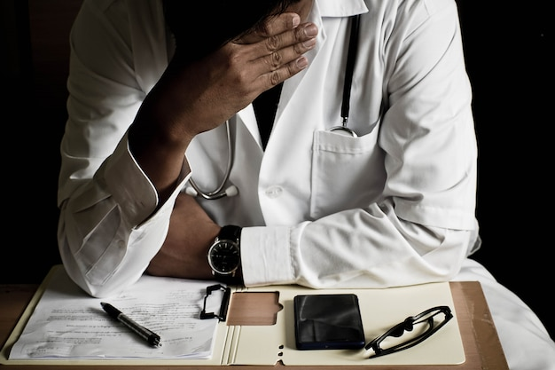 Sérieux docteur t assis stressé à cause du travail. style de clé faible