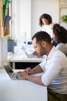 Sérieux employé masculin travaillant sur un projet dans le bureau