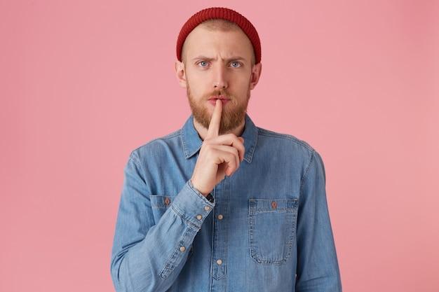 Sérieux gars barbu sans émotion calme en chemise en jean montrant le geste de silence, demande de garder la confidentialité secrète mettant le doigt sur les lèvres, isolé