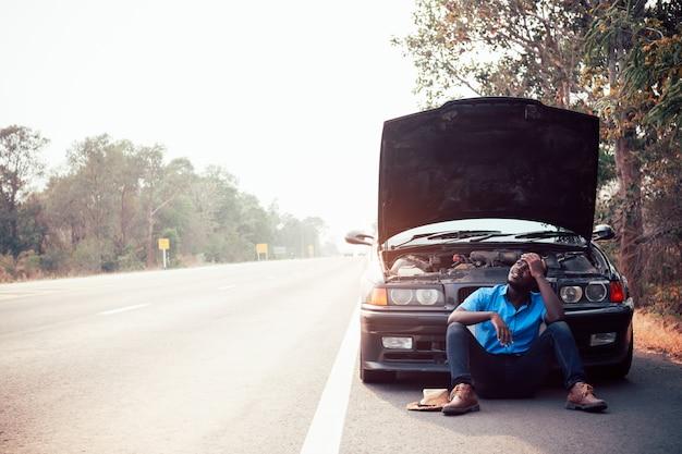 Sérieux, homme africain, tenant tête, mains, debout, près, vieux, voiture cassée