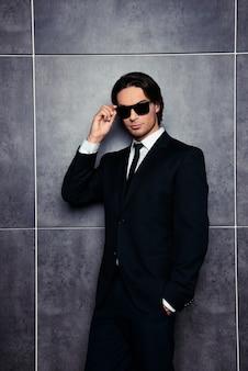 Sérieux homme élégant tenant des lunettes sur l'espace gris