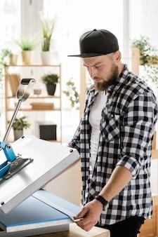 Sérieux jeune artisan tenant une bande avec un décor tout en l'imprimant sur un nouveau collier pour animaux de compagnie sur un équipement spécial par lieu de travail