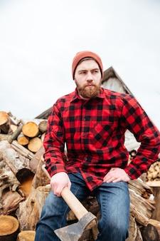 Sérieux jeune bel homme en chemise à carreaux assis sur des bûches et tenant une hache