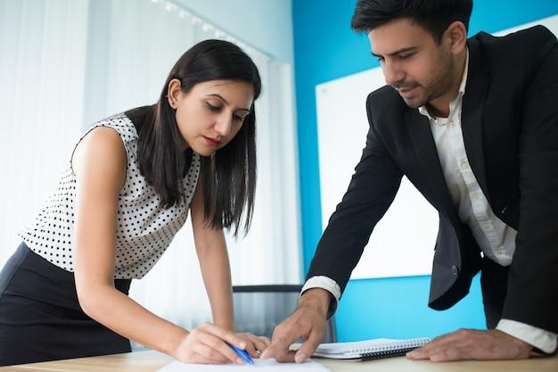 Sérieux jeune cadre vérifiant le document avec sa secrétaire