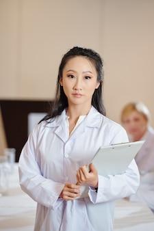 Sérieux jeune chercheur asiatique avec presse-papiers dans les mains regardant la caméra