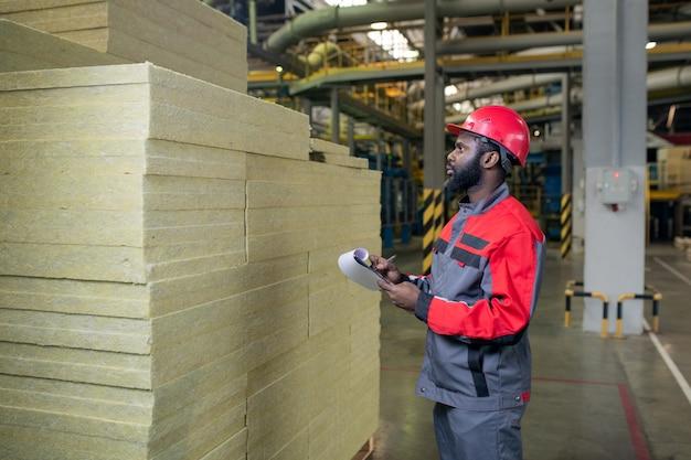 Sérieux jeune constructeur noir barbu comptant les matériaux de chaleur produits et prendre des notes dans le presse-papiers