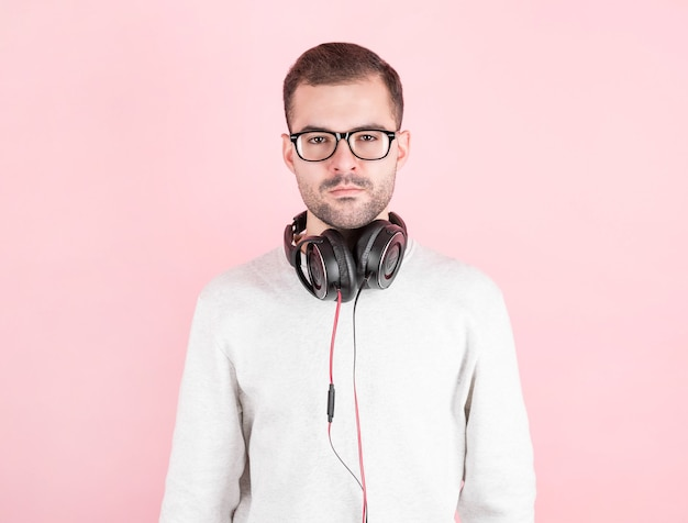 Sérieux jeune enfant mignon écoutant de la musique dans de gros écouteurs blancs sur un mur rose, en sweat-shirt blanc, journée mondiale du dj