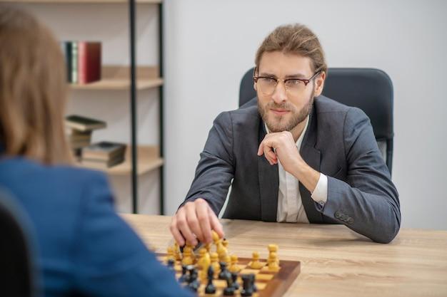 Sérieux jeune homme adulte dans des verres avec pièce d'échecs en main et adversaire à table de bureau