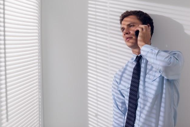 Sérieux jeune homme d'affaires à l'aide de téléphone portable