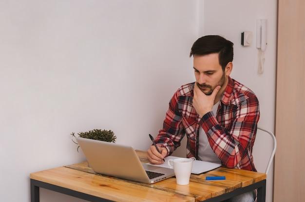 Sérieux jeune homme d'affaires assis et utilisant un ordinateur portable au bureau et prenant des notes