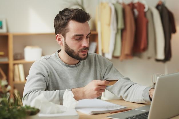 Sérieux jeune homme d'affaires regardant la carte de crédit alors qu'il était assis devant un ordinateur portable et va commander des médicaments en pharmacie en ligne