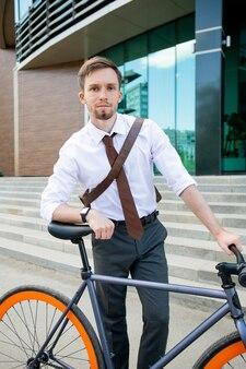 Sérieux jeune homme d'affaires vous regarde en s'appuyant sur son vélo contre l'escalier et l'extérieur du bâtiment