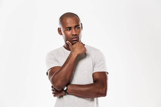 Sérieux jeune homme africain debout isolé