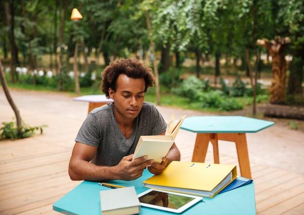 Sérieux jeune homme assis et étudiant dans le parc